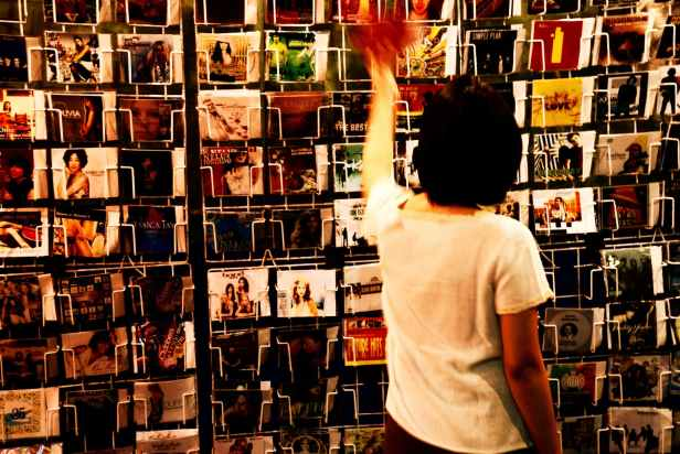 person wearing white shirt holding vinyl albums